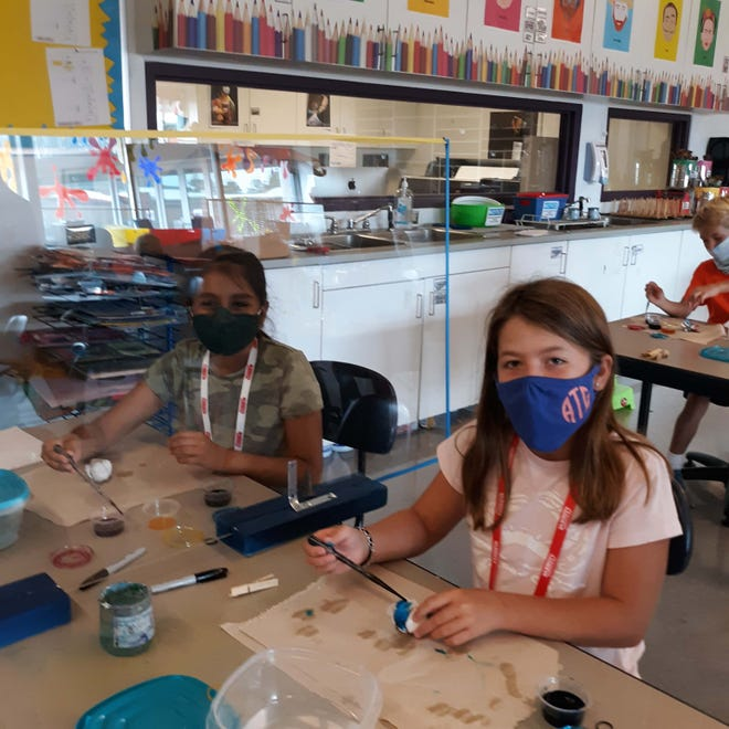 From left, Parrott Academy fourth graders Veda Patel and Alli George Thomas carefully apply dye to personalize their face masks. [CONTRIBUTED PHOTO]