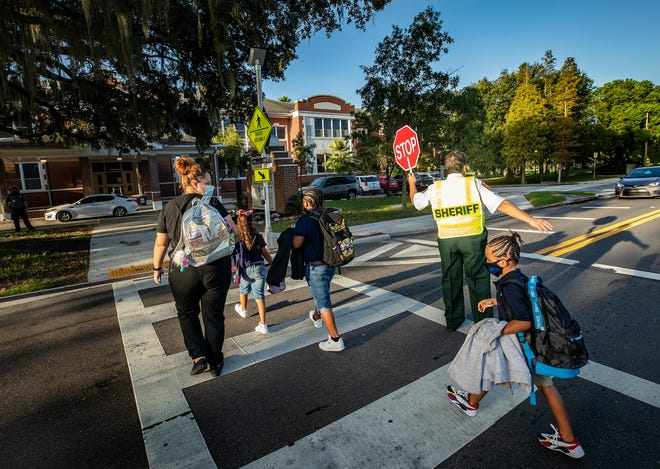Parents accompany their children to class during the first day of school at Dixieland Elementary in Lakeland on Aug. 24.