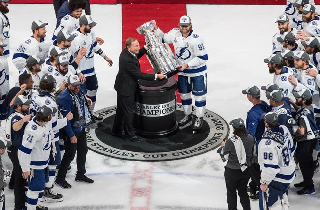 Tampa Bay Lightning's Steven Stamkos (91) is presented the Stanley Cup from NHL commissioner Gary Bettman as they celebrate after defeating the Dallas Stars in the NHL Stanley Cup finals.