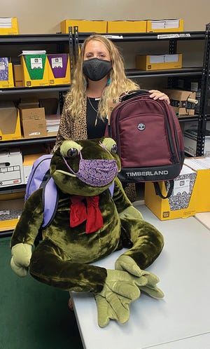 The winner of the ADFAC 'Guess the Number of Backpacks' contest, Kristen Hensley, is presented with the prize Timberland backpack by the School Supply Mascot, Addy the frog.
