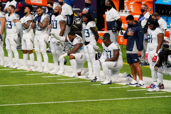 Members of the Tennessee Titans take part in the national anthem before an NFL football game against the Minnesota Vikings, Sunday, Sept. 27, 2020, in Minneapolis. The NFL says the Tennessee Titans and Minnesota Vikings are suspending in-person activities after the Titans had three players test positive for the coronavirus, along with five other personnel. The league says both clubs are working closely with the NFL and the players' union on tracing contacts, more testing and monitoring developments. The Titans are scheduled to host the Pittsburgh Steelers on Sunday. (AP Photo/Jim Mone)