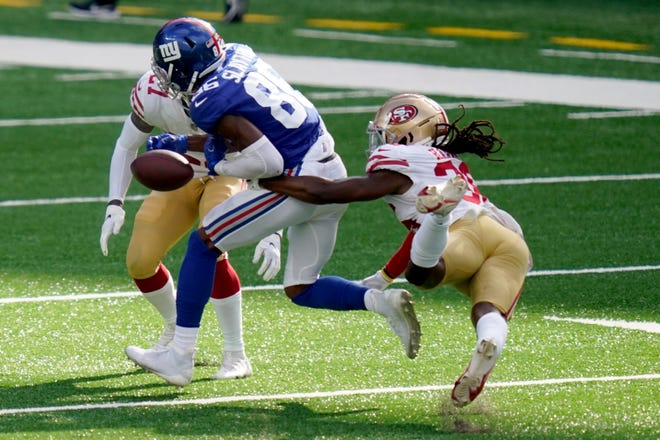 San Francisco 49ers' Marcell Harris, right, punches the ball away from New York Giants' Darius Slayton during the second half  Sunday in East Rutherford, N.J. The Giants are 0-3 following Sunday's loss.