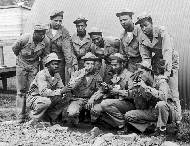A party of African American troops enjoying a song led by Private Manuel M. Diaz, of New Orleans, with his guitar, at their camp in August 1942 in Northern Ireland. [AP FILE PHOTO]