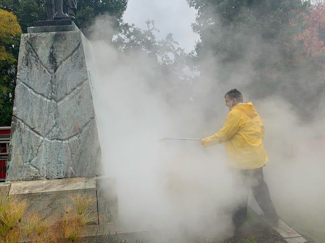 Utica Mayor Robert Palmieri cleans off graffiti from a Christopher Columbus statue Tuesday, Sept. 29, 2020 at Parkway and Mohawk Streets in Utica.