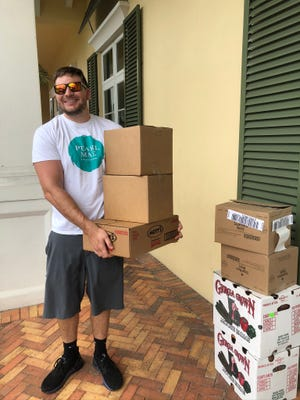 Volunteer Zachary Finnel unloads food that was donated from the Palm Beach County Food Bank to the Pearl Mae Foundation.