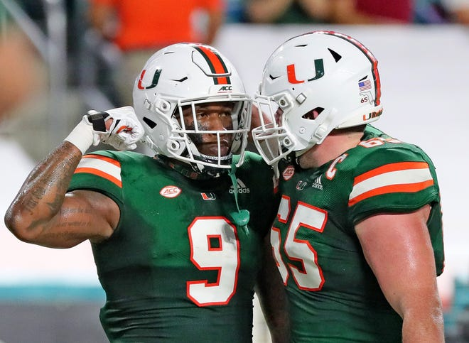UM's tight end Brevin Jordan (9) flexes after scoring a first quarter touchdown with offensive linemen Corey Gaynor (65) in the Hurricanes' victory over Florida State at Hard Rock Stadium in Miami Gardens.