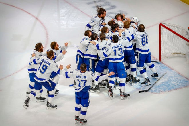 Lightning players mob goalie Andrei Vasilevskiy around the net after defeating the Stars 2-0 to capture the Stanley Cup Monday night at Rogers Place in Edmonton, Alberta