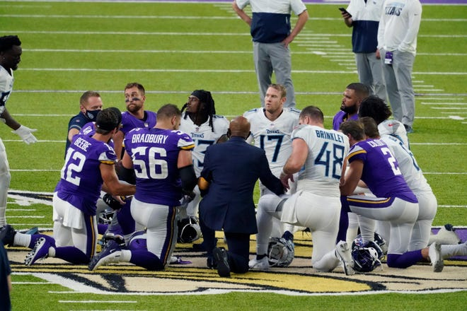 Tennessee Titans and Minnesota Vikings players meet at midfield following the Titans' 31-30 win over the Vikings on Sunday in Minneapolis.