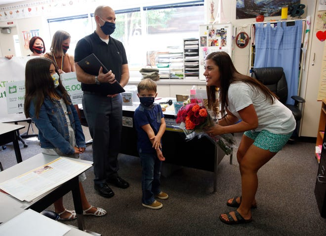 Nicole Butler-Hooton greets her family, daughter Avery Hooton, husband Matt Hooton and son, Beckett Hooton after they surprised her in second class classroom at Irving Elementary School after she was named Oregon Teacher of the Year.