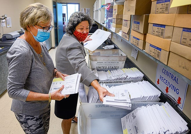 St. Johns County Deputy Supervisor of Elections Patsy Collins and Supervisor of Elections Vicky Oakes sort through vote-by-mail ballots received at the supervisor of elections office in St. Augustine on Monday.