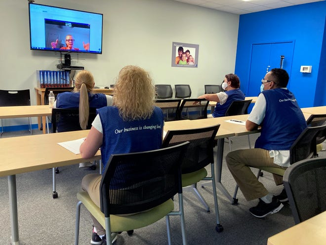 Instructor June Battersby, on the screen, reviews an exercise with Goodwill employees Yanet Sosa, left, Taimy Leon, Umiliana Rios and Samuel Bonilla-Cotto.
