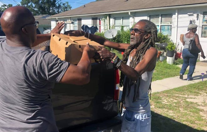 Vance Williams (left) of Sokoto House and Advance Youth Outreach helps deliver supplies to a community member in need earlier this summer. [CONTRIBUTED]
