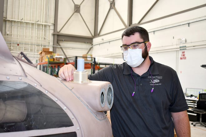 Tommy Stokes, a structures engineer on the H-60 Fleet Support Team at Naval Air Systems Command's In-Service Support Center at Fleet Readiness Center East, explains how this 3D-printed omnidirectional antenna mount secures to the MH-60S Seahawk multi-mission helicopter. The mount, developed by a team of H-60 FST engineers at FRCE, is part of a communications upgrade package that will be installed on more than 200 Navy aircraft. In support of the Full Motion Video system slated for installation on all Navy MH-60S Block 3 helicopters, the team developed three antenna mounts – two of them 3D-printed – and rack to secure the FMV system, developed by a defense contractor, to the aircraft. Photo by Heather Wilburn, Fleet Readiness Center East Public Affairs
