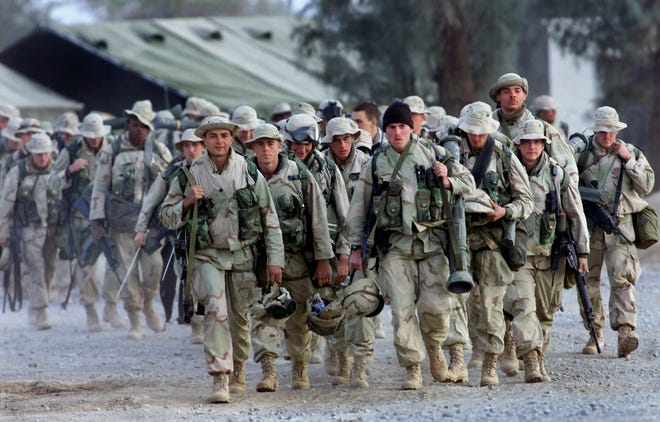 In this Dec. 31, 2001, photo, U.S. Marines with full battle gear prepare to leave the U.S. military compound at the Kandahar airport for a mission.