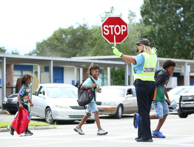 Students from Williams Elementary School cross Southeast Seventh Avenue as a crossing guard stops traffic after school on Tuesday in Gainesville.