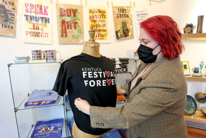 Ashley Williams, marketing manager for the Kentuck Art Center, puts a festival T-shirt on a mannequin for display in the store in Northport Tuesday, Sept. 29, 2020. While last year's festival was virtual, this year's festival will be held Saturday and Sunday at Kentuck Park in Northport, with masks required for entry. [Staff File Photo/Gary Cosby Jr.]