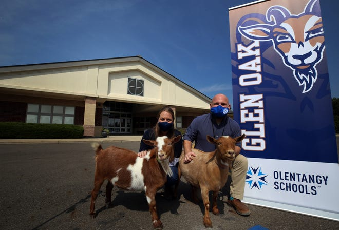 Glen Oak Elementary School assistant principal Anne-Marie Rhodes, with Ricky the goat, and principal Stephen Peters, with Lucy the goat, pose outside the school Sept. 23. The Goats became the new mascot of Glen Oak; the real goats belong to art teacher Jenna Magyar.