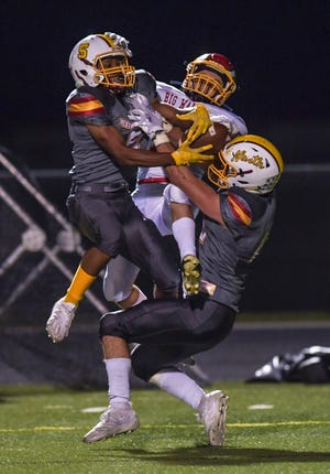 Westerville North's Ty O'Hearn (right) and Chris Campbell break up a pass intended for Big Walnut's Cam Gladden during the teams' game Sept. 25 . The Warriors won 20-17.