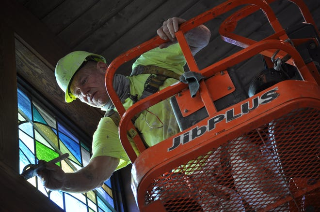 Butch LeCoumpte of Henry Painting Co. uses a brush to touch up stained glass frames near the ceiling of the newly constructed adoration chapel in St. Brendan the Navigator Catholic Church in Hilliard.