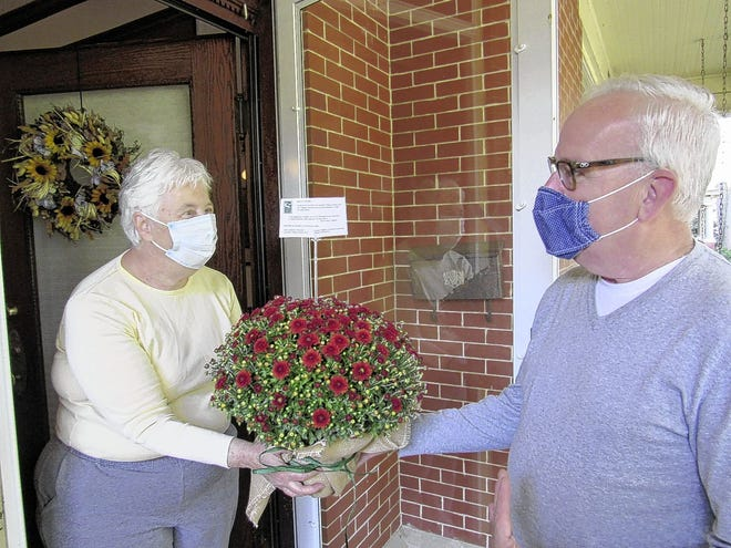 Meg Teaford accepts mums from Donald Wiggins, executive director of Village Connections, a concierge service for the aging population of German Village. Village Connections and the German Village Garten Club collaborated Sept. 21 on flower deliveries.