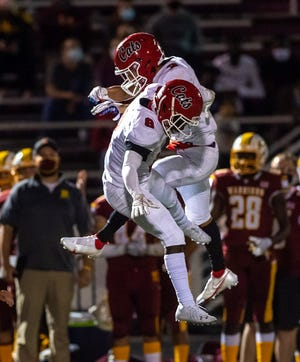 Westerville South's Enbrass Fofanah (left) and Brandon Armstrong celebrate the Wildcats' 32-28 win over host Westerville North on Sept. 11.
