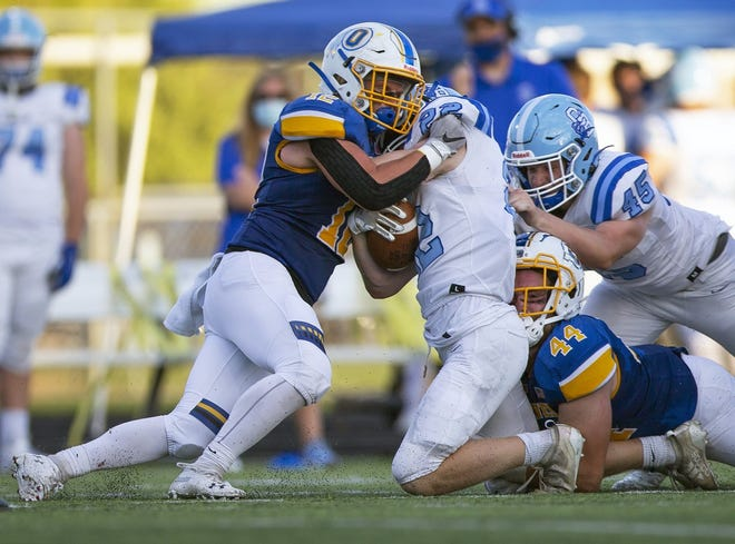 Olentangy's Luke Martin (left) and Ethan Hand team up to stop Gavin Angell of Berlin during their game Sept. 4. The Braves' defense held three of their first four opponents to seven points or fewer. Olentangy visits Marysville on Friday, Oct. 2, for a league title showdown.