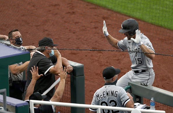 Adam Engel #15 of the Chicago White Sox celebrates socially distantly with teammates in the dugout after hitting a three--run home run during the 2nd inning of the game against the Kansas City Royals at Kauffman Stadium on July 31, 2020 in Kansas City, Missouri.