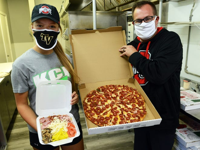 Chad Lynn and his daughter Jenna Wilson, left, hold pizza and salad from Buckeye Piez. Lynn and his wife, Johanne, opened the establishment, located off Dillon Hills and Clay Littick drives in Muskingum County, earlier this month.