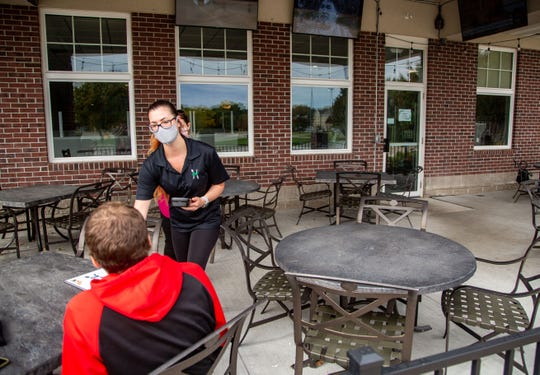 Courtney Plaskitt, a server at Health House Foods and Taste of New York in Johnston, helps a customer on the patio Tuesday, Sept. 29, 2020.
