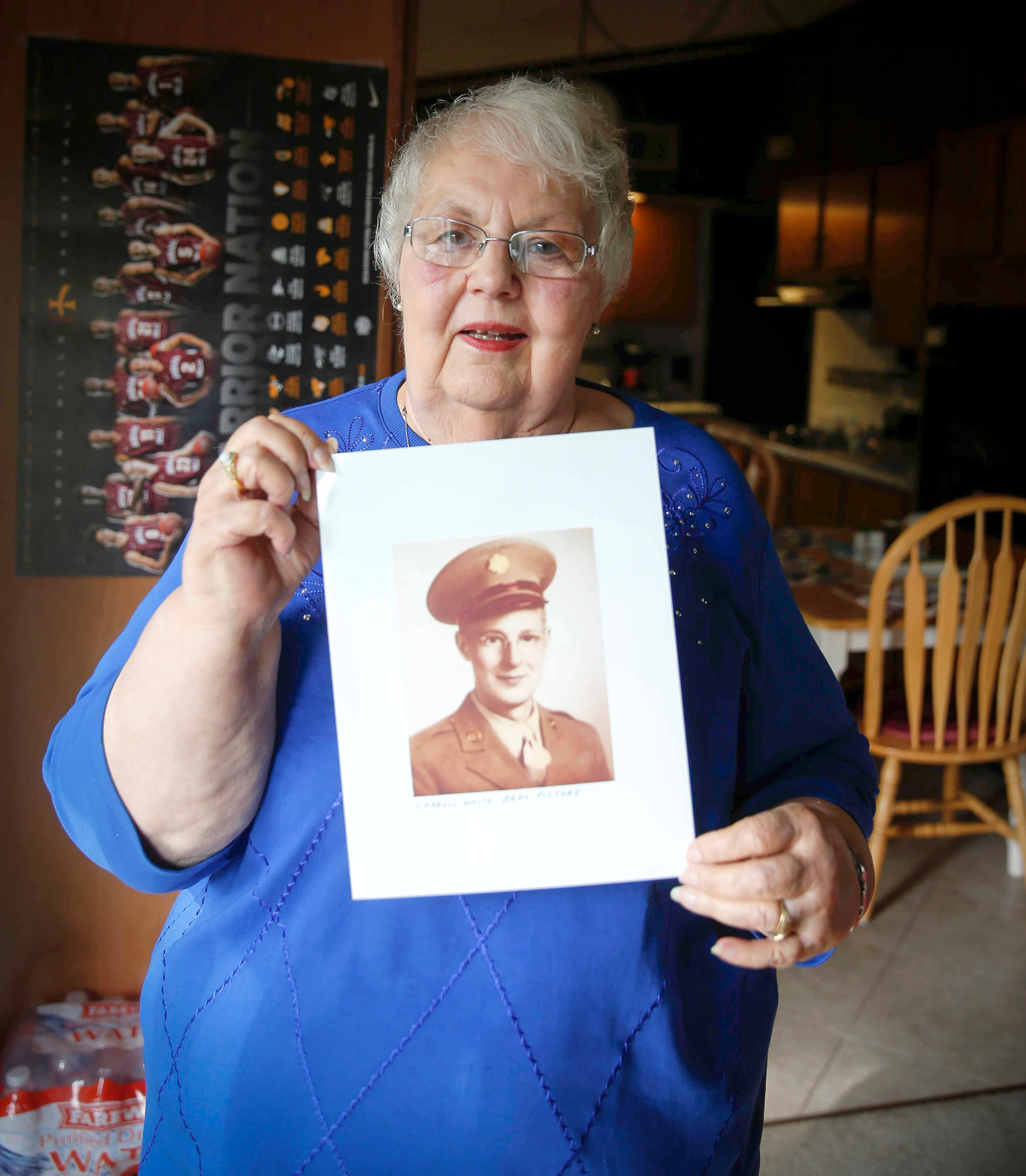 Lynne Blackwell poses for a photo with a portrait of her father, Carroll White, who died from COVID-19 shortly after his 100th birthday.