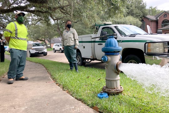 City workers Kristina Watson, right, and Lennie Miner, a maintenance foreman monitor Monday, Sept. 28, 2020, test water flowing out of a hydrant in Lake Jackson, Texas.