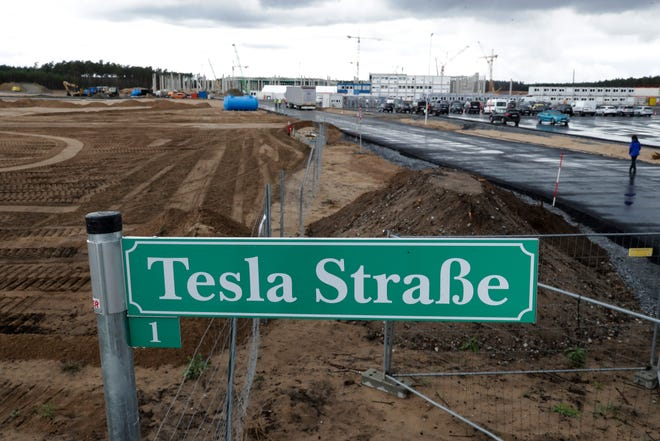 A street sign reading Tesla Street stands in front of the construction site for Tesla's new Berlin factory.