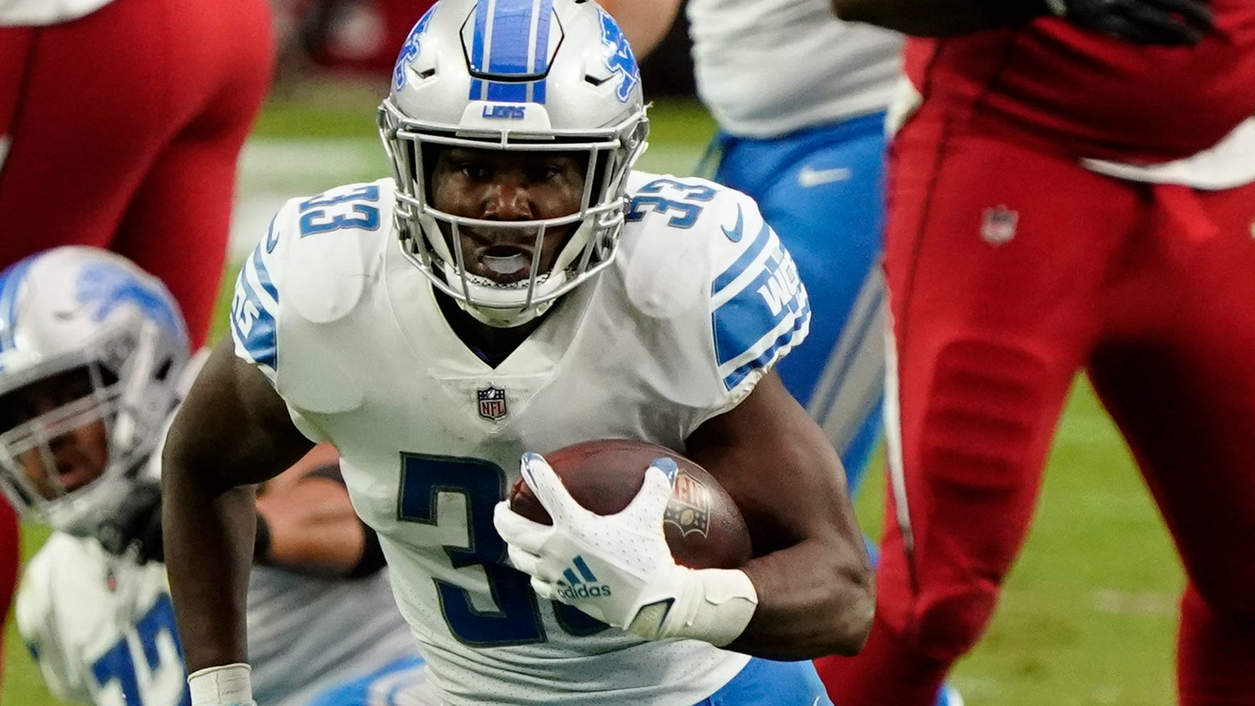 Running back Kerryon Johnson (33) remains the starter in the Lions' backfield that also features D'Andre Swift and Adrian Peterson.