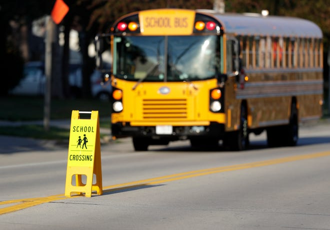 A school crossing sign sits in the road as a bus goes by near Bay View Middle School on Sept. 1, 2020, in Howard, Wis.