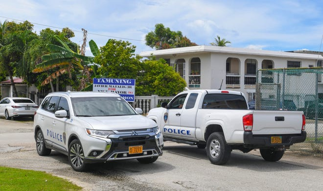 Guam Police Department officers gather for a quick meeting at an intersection as they conduct a search following reports of a shooting incident on Tuesday, Sept. 29, in Tamuning.