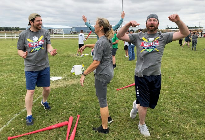 Randy Tasa (right) of The Guv Daddies celebrates hitting a game-winning home run while teammates Steve Gold (left) and Kelly Schneider cheer following a game during the Henderson Wiffle Ball Classic on Saturday at the Henderson County Fairgrounds. (Photo by Chuck Stinnett)