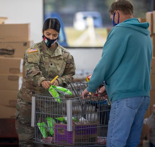 National Guard soldier Marissa Lopez fills a cart at Old Bethel & Partners food pantry in Indianapolis on Tuesday, Sept. 29, 2020.