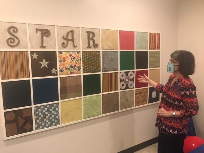 Judy Duke talks about the different squares on the board in the sensory room at The Star Center.