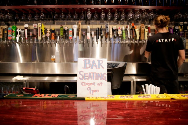 A sign sits on the bar of The Tap to advise customers of the Tippecanoe County Health Order that closes bar seating at 9 p.m. every night, Wednesday, Sept. 23, 2020 in West Lafayette.