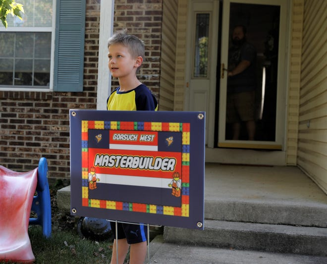 Noah Bennett, a third-grader at Gorsuch West Elementary, poses with the Masterbuilder sign outside his house Monday, Sept. 28. Bennett was honored as one of the Masterbuilders of the week, as part of a program honoring students going above and beyond in their school work.