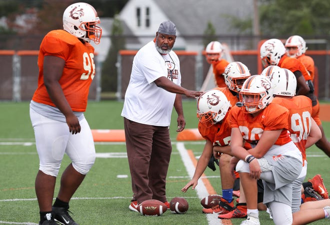 DeSales offensive coordinator Ty Scroggins, center, gives instruction to the offensive line during practice at the school in Louisville, Ky. on Sept. 22, 2020.