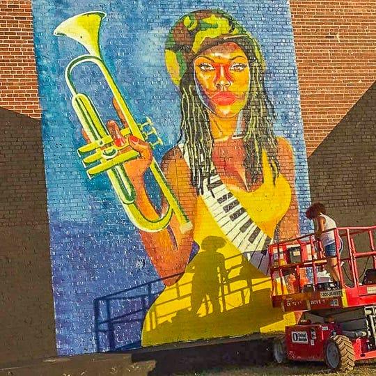 Jamie Bonfiglio works on her mural in Birmingham, Al.