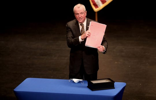 Governor Phil Murphy holds up the signed budget, in Trenton, Tuesday, September 29, 2020.
