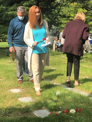 Beth Hool of Livonia places a flower at a grave site during the Sept. 12 Day of Remembrance event.
