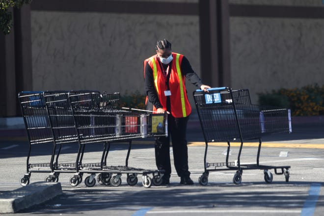 An Albertsons grocery store employee collects shopping carts in the parking lot in Palm Springs, Calif. on Tuesday, September 29, 2020, during the COVID-19 pandemic.