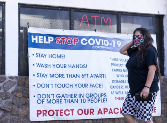 A woman walks into a White Mountain Apache Tribe gas station where a sign indicates practices to help stop the spread of COVID-19.