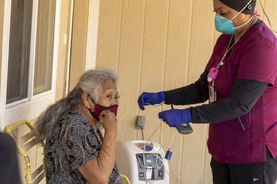 Victoria Moses, a health tech with the White Mountain Apache Tribe, checks the oxygen levels of Eugenia Cromwell, 78, outside her home.
