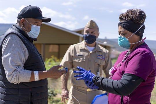Victoria Moses, a health tech, checks on COVID-19 patient Timothy Coawson Jr., along with hospital spokesperson Lt. Commander Justin Tafoya, outside Coawson's White Mountain Apache Tribe home.