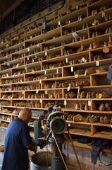 A bootmaker is shown in front of a wall of wooden lasts at M.L. Leddy.