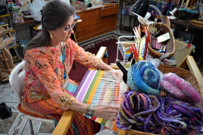An artist is shown weaving at the Chicken Farm Art Center in San Angelo.